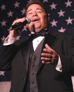 "Tenor Daniel Rodriguez sings ""God Bless America"" during the USO Metro awards in Arlington, Va., March 25, 2008. DoD photo by Air Force Tech. Sgt. Adam M. Stump. (Released)"