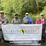 men fishing holding banner